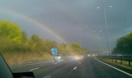 雨上がりに道路から虹が生えている画像